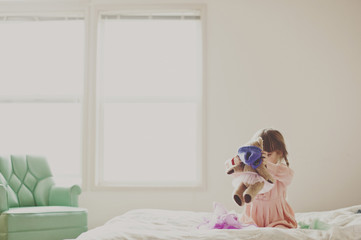 Girl playing with teddy bear in bedroom at home