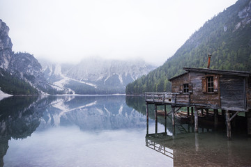 Wooden house by calm lake and mountains