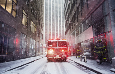 Illuminated headlights of fire engine in city during winter