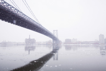Williamsburg Bridge over river in foggy weather