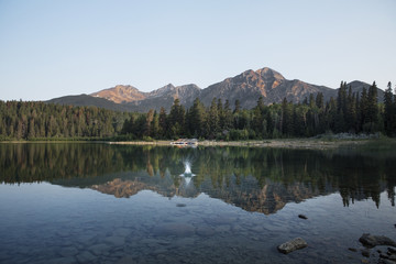 Reflection of mountains and trees in lake against clear sky