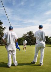 Golf Caddies Watching a Golfer Putt