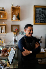 Happy hispanic barista working at a coffee shop