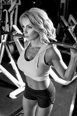 Black and white image of woman working out in a gym