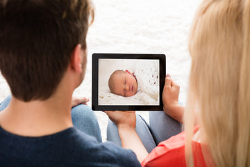 Couple Looking At Baby's Photo On Digital Tablet