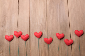 Valentines day concept of red heart shape decorations with old wood floor background.
