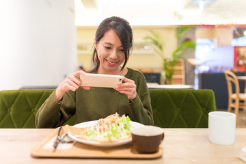 Woman taking photo before enjoy her salad
