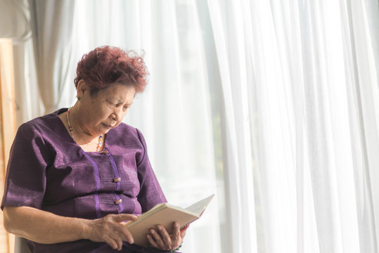 Asian senior woman reading a book with window light and vintage