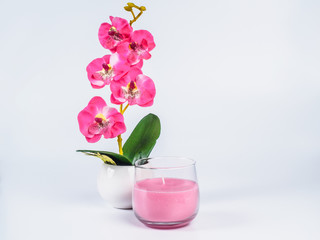 Picture of the orchid with pink candle in a glass on white background. Handmade orchid with candle in a glass close up.