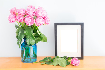Violet fresh roses with empty photo frame on wooden shelf