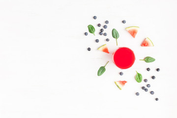 Watermelon juice, blueberry, watermelon slices and spinach leaves on white background. Summer concept. Flat lay, top view