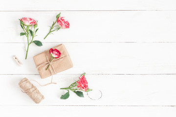 Flowers composition. Gift and rose flowers on wooden white background. Flat lay, top view