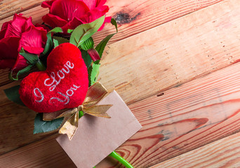Paper for your text and small red hearts, rose on old wood backg