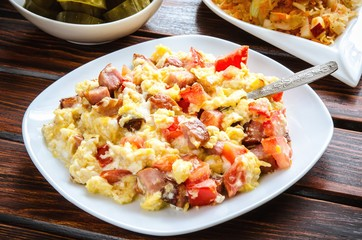 Tasty breakfast in the morning. Scrambled eggs with sausage and tomatoes on a wooden table.