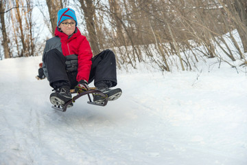 Boy in glasses riding the hills on sleds in winter.