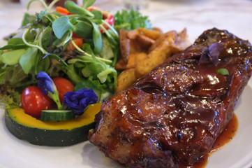 Grilled pork  spicy salad , French fries and  vegetables salad  , Thai fusion food