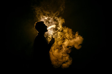The man smoke an electric cigarette against the background of the flame