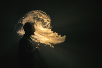 The man smoke an electric cigarette on the background of the flame