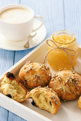 Home breakfast - homemade cheese bread rolls with cranberries, almond ans sunflower seeds and cup of coffee.