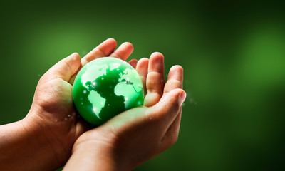 Save world save life concept.The globe in hands with green color background