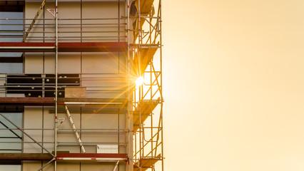 Baugerüst auf einer Baustelle Gewerbebau mit Sonnenstrahlen im Gegenlicht