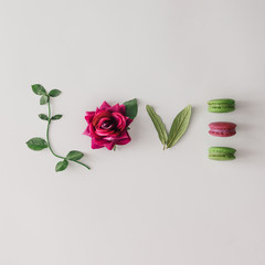 Word LOVE made out of flower, leaves and macarons. Flat lay. Lov