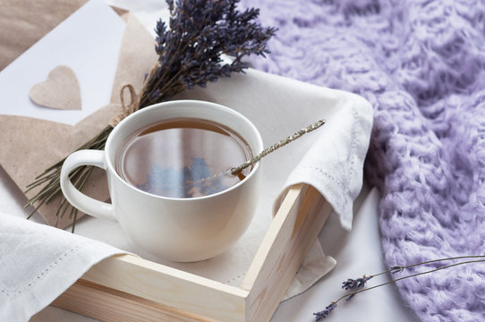 A tray with a cup of hot tea and lavender love letter in bed with a knitted blanket