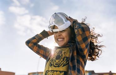 Laughing girl putting on baseball cap