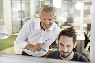 Two smiling men in office looking at computer monitor