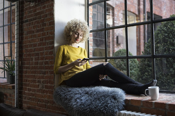 Young woman sitting on window sill, using smart phone