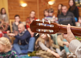 Company of  friends listening a female guitarist singing song