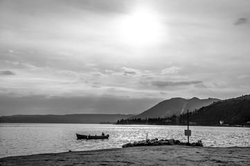 Paesaggio in bianco e nero di una sera d'estate sul lago di Garda con la barca solitaria sulla superficie dell'acqua