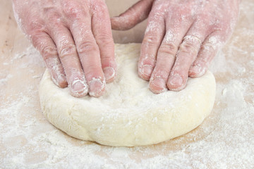 Pizza baking , starting to stretching dough on floured wooden board