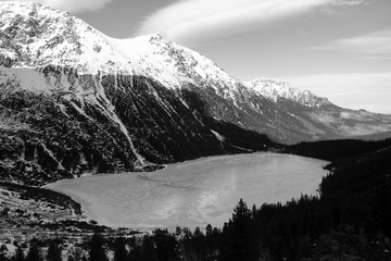 Black and white panorama of winter mountains. view on frozen lake