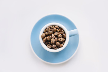 macro view of a blue espresso cup filled with freshly roasted coffee beans on a white background