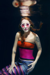 red hair funny girl in colorful clothes and pink sunglasses with tatto on the dark background swimming underwater with photo camera