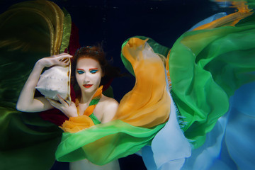 Red hair girl with big sea shell in colorful clothes on the dark background underwater