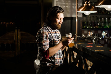 a bearded man looking smartphone and keep a glass of beer