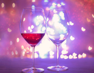 Two glasses with wine with hearts shaped bokeh background. St. Valentine's Day.