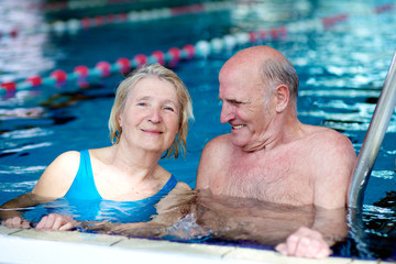Happy healthy active senior couple having fun together in the swimming pool