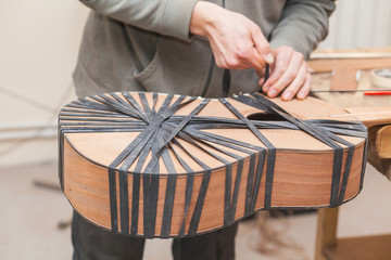 Serious professional guitar-maker working with unfinished guitar at workshop