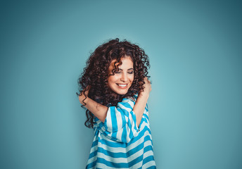 Closeup portrait confident smiling woman holding hugging herself isolated blue wall background. Positive human emotion, facial expression, feeling, reaction, situation, attitude. Love yourself concept