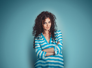 Portrait of curly young gorgeous brunette woman isolated over blue background wall.