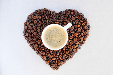 Coffee beans in the shape of a heart and a cup of freshly brewed coffee.