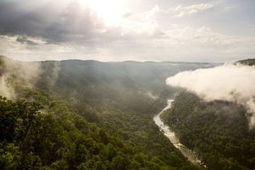 The sun rises over the New River Gorge on a misty, rainy morning in West Virginia.