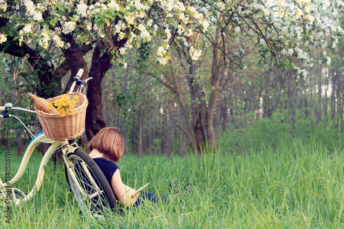healthy lifestyle weekend/ People who arrived on a bicycle, resting reading a book in the park under a blossom  tree