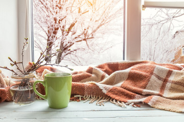 Cup of coffee, books, branch of cherry tree, wool blanket on windowsill. In the background snow tree pattern on window. Cozy home concept.