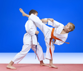 Children in karategi are training blows arm and leg