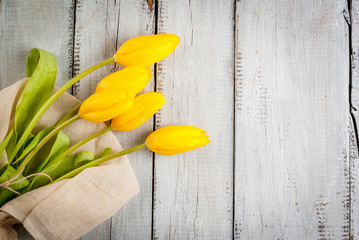 Bouquet of spring flowers tulips, on a white rustic table, top view, copy space