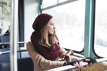 Beautiful young woman sitting in tram and looking through window.